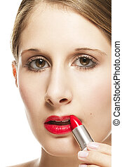 closeup of a beautiful woman applying lipstick on white background