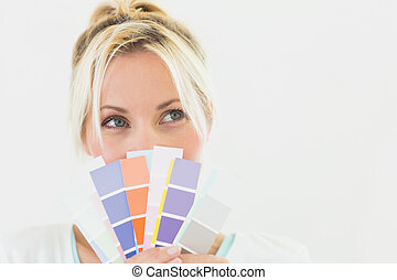 Closeup of a beautiful young woman holding color swatches