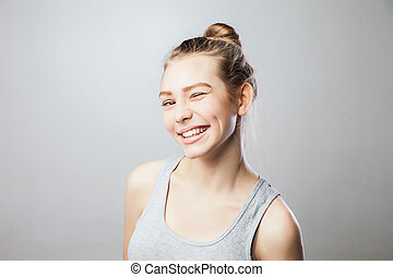 Closeup of a beautiful young woman winking. Isolated over ...