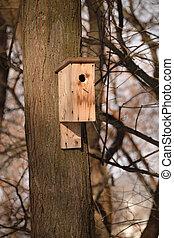 Closeup of a birdhouse on a trunk
