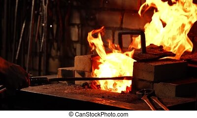 Closeup of a blacksmith fanning the flames of the furnace,...