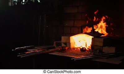 Closeup of a blacksmith fanning the flames of the furnace, using the tools prevents embers, sparks flying to the side in slow motion. Close-up of blacksmith's hand