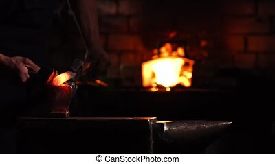Closeup of a blacksmith's hammer on the background of burning flames of the furnace