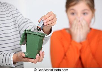 Closeup of a boy putting a battery in a miniature bin much...