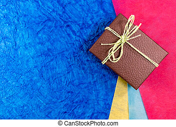 Closeup of a brown gift box on colored papes in background with copy space. Mother's day gift concept.