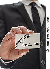 Closeup of a business man handing card with Call us message