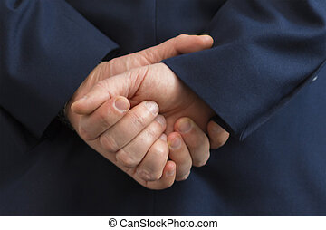 Closeup of a business man with his hands behind his back.