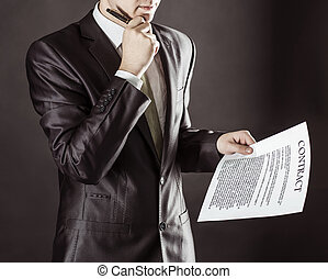 closeup of a businessman holding a pen and a document with the terms of the contract.