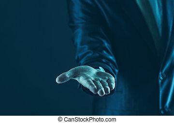 closeup of a businessman stands and extends a hand forward.