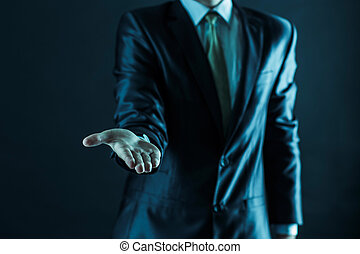 closeup of a businessman stands and extends a hand forward.