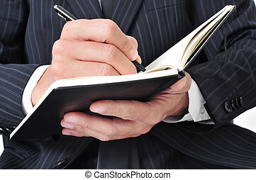businessman writing in a notebook
