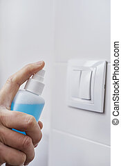 closeup of a caucasian man disinfecting the light switch by spraying a blue sanitizer from a bottle
