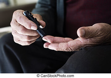 old man about to measure his blood glucose level - closeup ...
