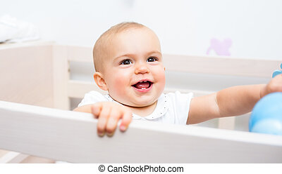 Closeup of a cheerful cute baby in the crib