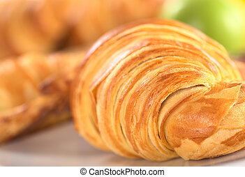 Closeup of a croissant with a green apple in the background (Selective Focus, Focus on the front of the right croissant)