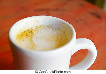 Closeup of a cup of cappuccino coffee on colorful table