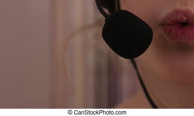 Closeup of a cute little girl in headphones singing in a microphone. 4K