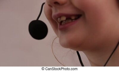 Closeup of a cute little girl in headphones singing in a microphone.