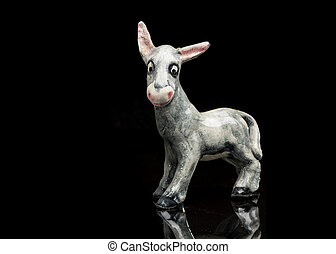 Closeup of a cute porcelain donkey standing on a reflective surface