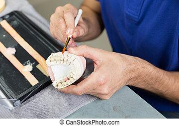 Closeup of a dental technician applying porcelain to a mold