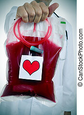 doctor holding a blood bag with a sticker of a red heart -...