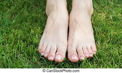Closeup of a female feet with white french pedicure on nails