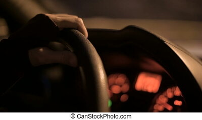 Closeup of a female hand holding the steering wheel driving a car on a country road at night. Shallow depth of field