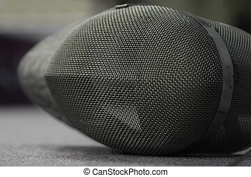 Closeup of a wire mesh fencing mask used in the sport of fencing to protect the face from a weapon thrust