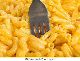 closeup of a fork in a pile of macaroni and cheese