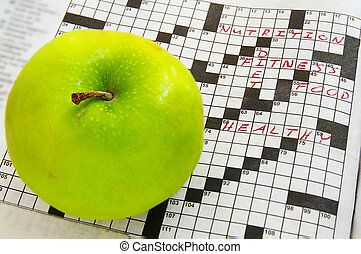 closeup of a fresh green apple and crossword puzzle