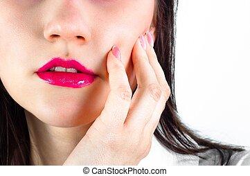 Closeup of a girl holding her cheek