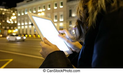 Closeup of a girl looking for information on the tablet in the evening city