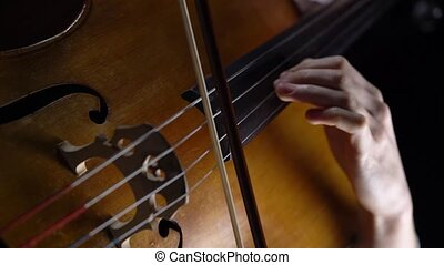 Closeup of a girl playing the cello in dark studio