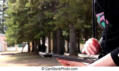 closeup of a girl using tablet in the park