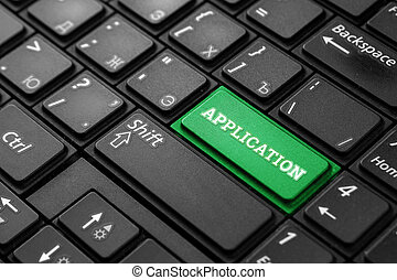 Closeup of a green button with the word application, on a black keyboard. Creative background, copy space. Concept of magic button, development, technology.
