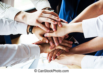 Closeup of a group of businesspeople joining their hands together.