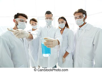 closeup of a group of medical workers working with liquids