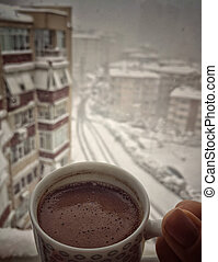 hand holding a cup of coffee against city view under snow in winter