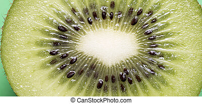 Closeup of a kiwi fruit on a green background
