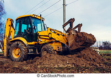 Closeup of a large bucket excavator digging the ground to set the road.