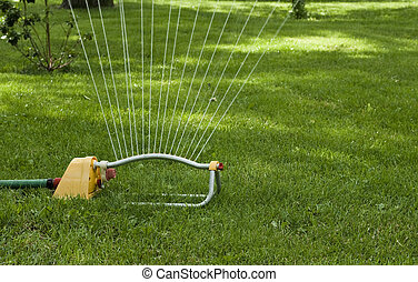 lawn sprinkler - closeup of a lawn sprinkler watering the...