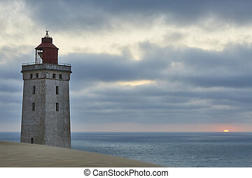 Closeup of a lighthouse with the sunset in the back