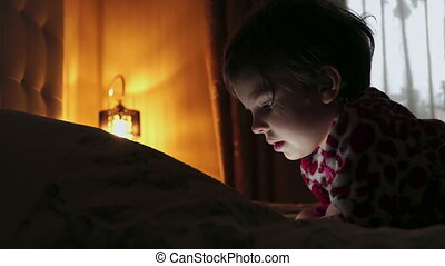 Closeup of a Little cute girl in full darkness watching tablet