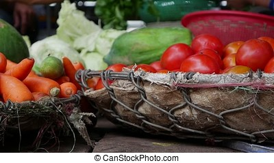 Closeup of a lot of vegetables in wicker baskets on the local market