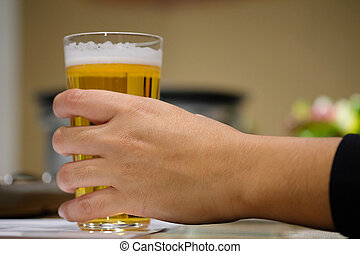 Closeup of a male hand holding a glass of beer