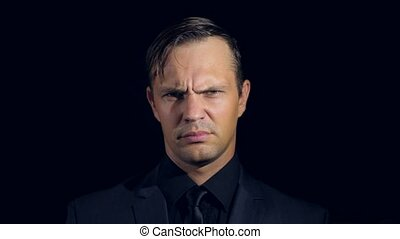 closeup of a man in black clothes on black background. 4k. Slow motion. man shrugs indignantly, and closes the camera with his hand.