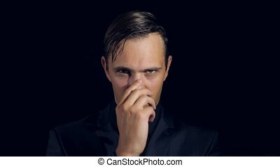 closeup of a man in black clothes on black background. 4k. Slow motion. man strokes his nose and looks at the camera. lie gesture