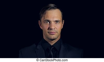 closeup of a man in black clothes on black background. 4k....