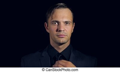 closeup of a man in black clothes on black background. 4k. Slow motion. man adjusts his tie, smiles and looks into the camera