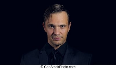 closeup of a man in black clothes on black background. 4k. Slow motion. man beckons his finger to himself, smiles and looks into the camera